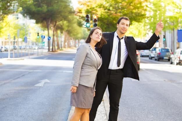 Colegas de trabalho confiante pegar táxi e pé na estrada Foto gratuita