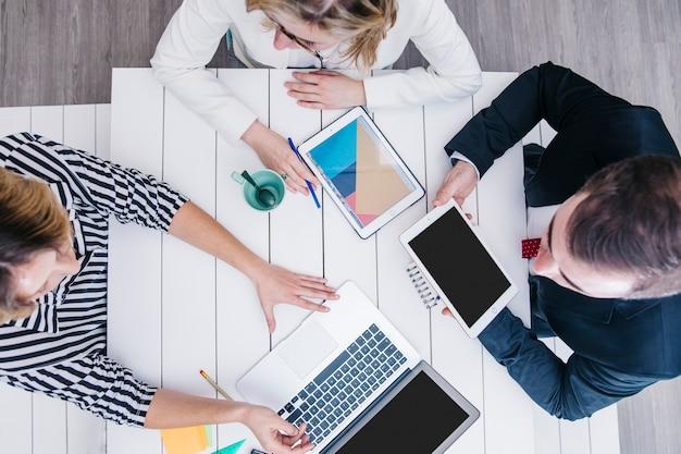Colegas de trabalho conversando e usando gadgets na mesa Foto gratuita