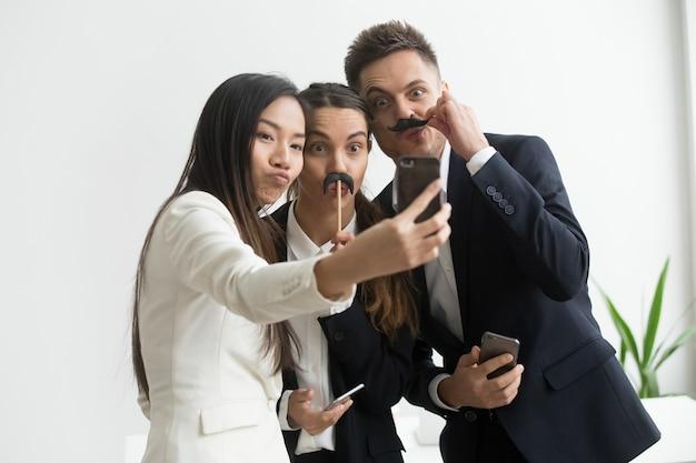 Colegas de trabalho fazendo foto com acessório bigode Foto gratuita