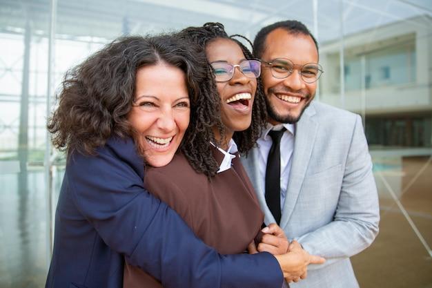 Colegas de trabalho feliz abraçando Foto gratuita
