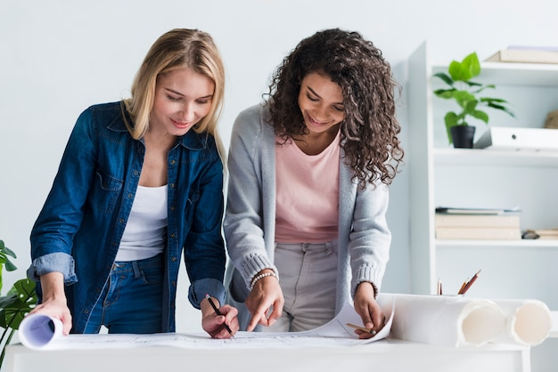Colegas de trabalho femininas, inclinando-se sobre o desenho de planta de papel Foto gratuita