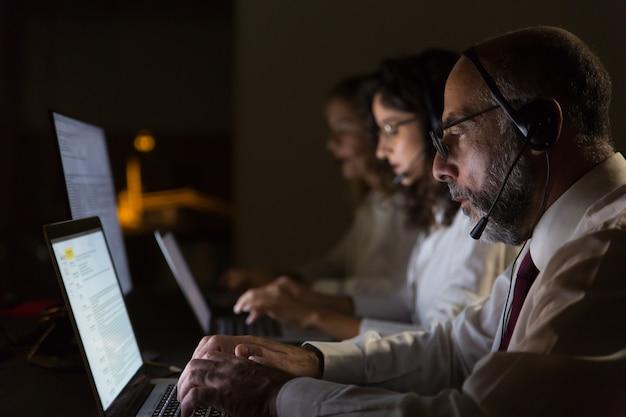 Colegas de trabalho focados em fones de ouvido digitando em laptops Foto gratuita