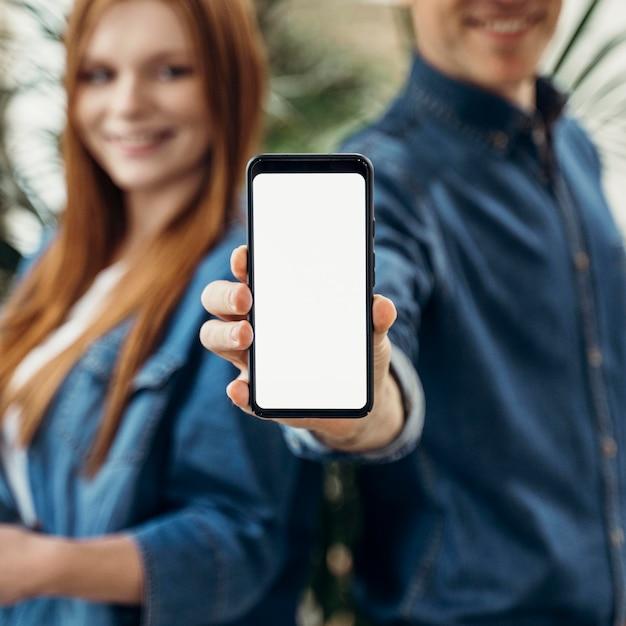 Colegas de trabalho mostrando um telefone com tela vazia Foto gratuita