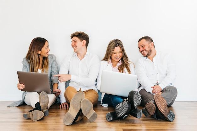Colegas de trabalho multirraciais sentado com laptops no chão Foto gratuita