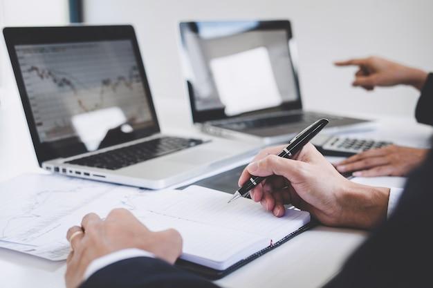 Colegas de trabalho, trabalhando com laptop, discutindo e análise de gráfico de negociação no mercado de ações Foto Premium