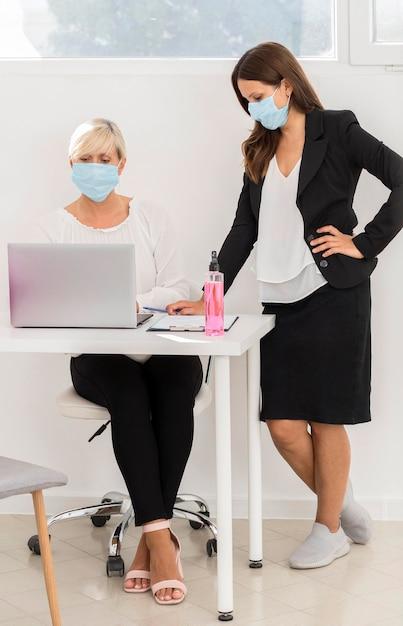 Colegas de trabalho usando máscara de proteção e trabalhando Foto gratuita