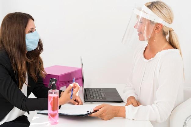 Colegas de trabalho usando máscara médica e protetor facial Foto gratuita