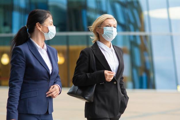 Colegas de trabalho usando máscaras e ternos de escritório, encontrando-se e caminhando juntos pela cidade, conversando, discutindo o projeto. tiro médio. conceito de negócios e coronavírus Foto gratuita