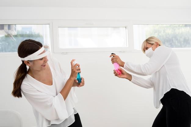 Colegas de trabalho usando proteção facial e brincando com desinfetante para as mãos Foto gratuita
