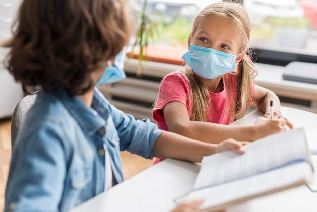 Colegas fazendo sua lição de casa usando uma máscara médica Foto gratuita