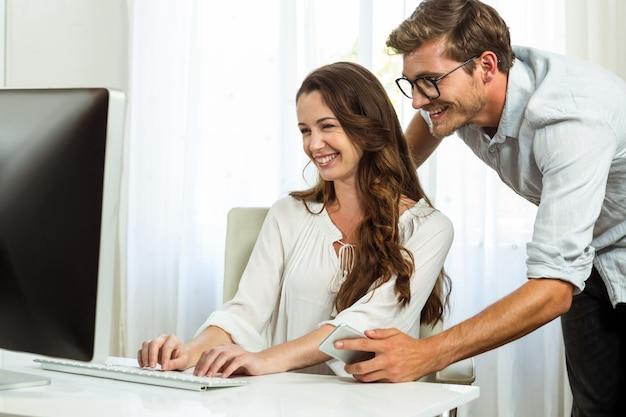 Colegas felizes usando o computador no escritório Foto Premium