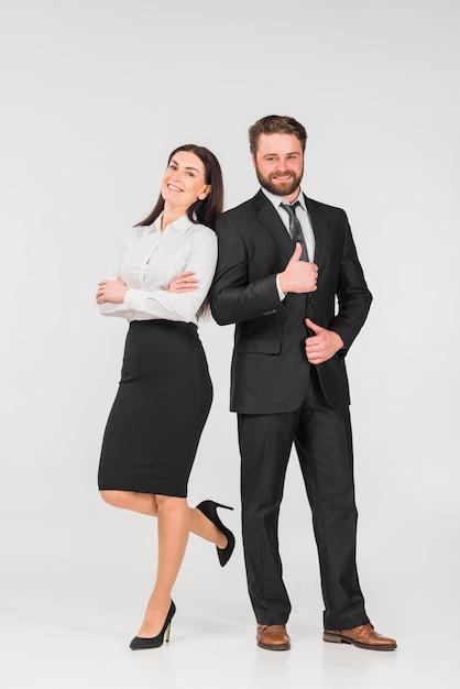 Colegas homem e mulher, inclinando-se uns aos outros e sorrindo Foto gratuita