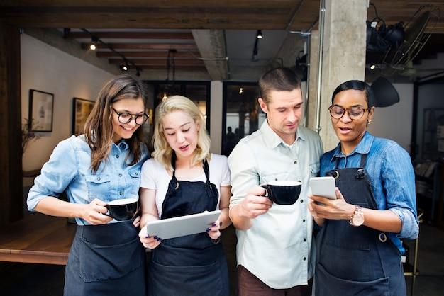 Colegas jogando em dispositivos digitais em uma loja de café Foto Premium