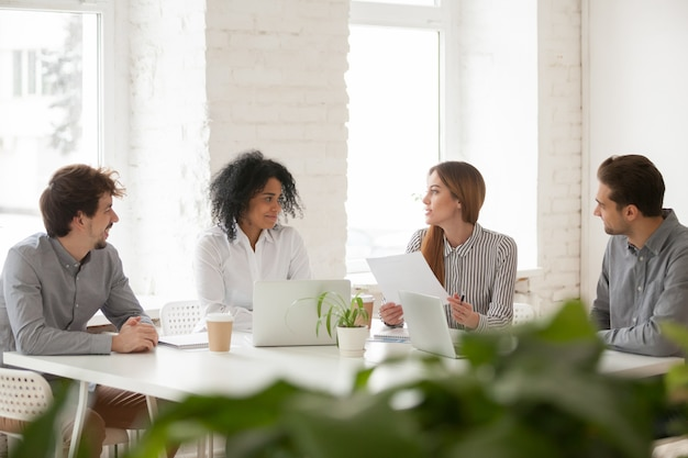 Colegas masculinos e femininos multirraciais, tendo a discussão na reunião de equipe Foto gratuita