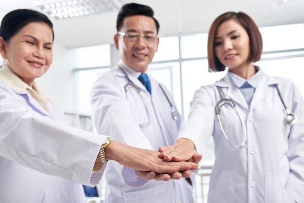 Colegas médicos de apoio que empilham as mãos para mostrar a colaboração são a chave do sucesso Foto gratuita
