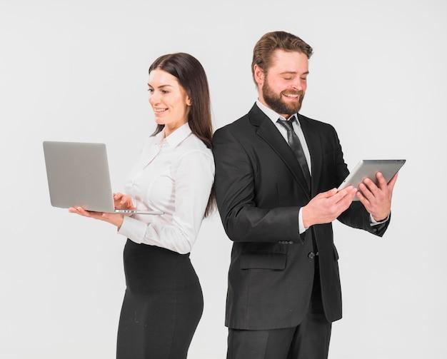 Colegas mulher e homem em pé com dispositivos Foto gratuita