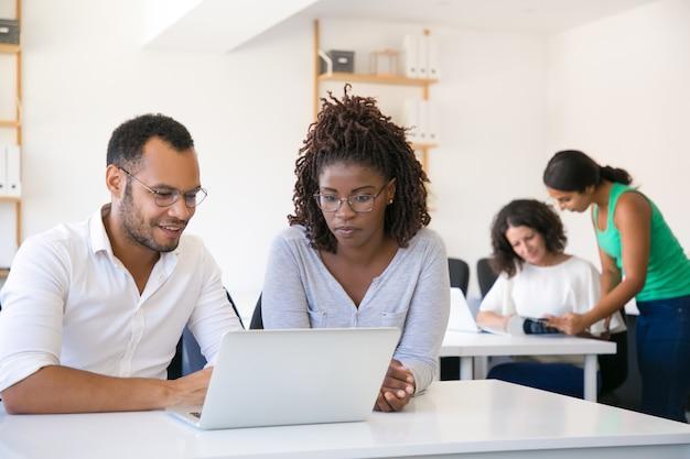 Colegas multiétnicas, olhando para a tela do laptop Foto gratuita