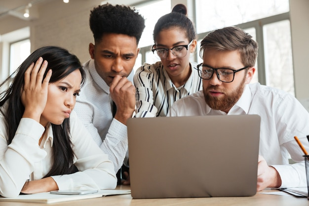 Colegas nervosos novos do negócio que usam o computador portátil. Foto gratuita