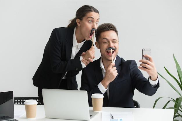 Colegas que fazem autorretrato com acessório de bigode Foto gratuita
