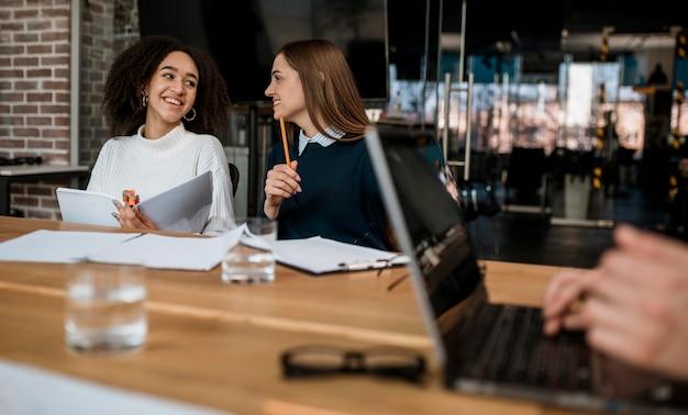 Colegas sorridentes conversando entre si durante uma reunião Foto gratuita