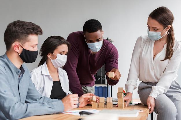 Colegas tendo uma reunião no escritório durante a pandemia com máscaras médicas Foto gratuita