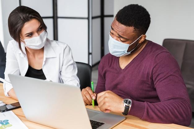 Colegas trabalhando juntos durante a pandemia no escritório com máscaras Foto gratuita