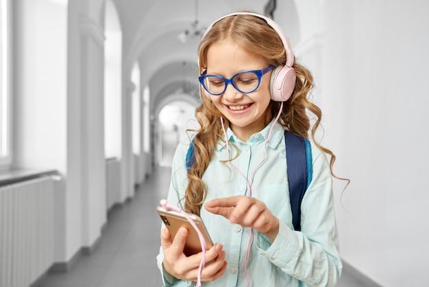 Colegial com segurando o telefone de chamada e ouvir música Foto Premium