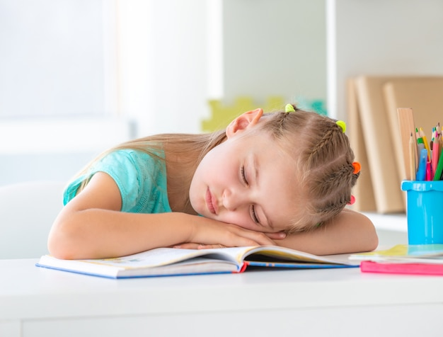 Colegial está dormindo no livro aberto Foto Premium