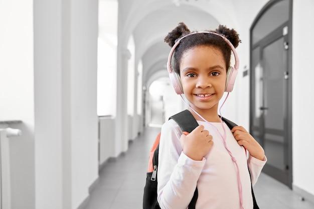 Colegial usando fones de ouvido em pé no corredor Foto Premium