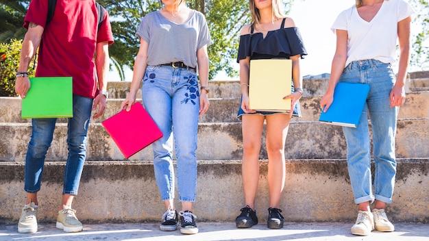 Colheita de estudantes com livros em pé em etapas Foto gratuita