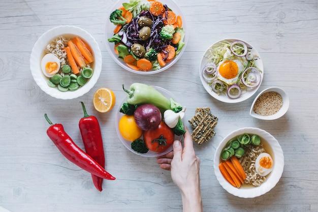 Colheita de mão colocando legumes perto de pratos Foto gratuita