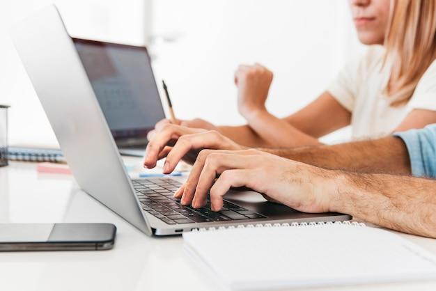 Colheita de mãos digitando no laptop no local de trabalho Foto gratuita
