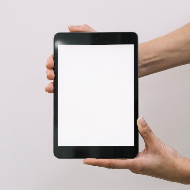 Colheita de mãos mostrando tablet vazio Foto gratuita
