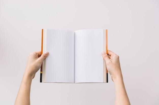 Colheita de mãos segurando o livro aberto Foto gratuita