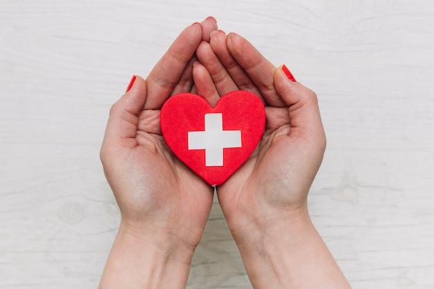 Colheita de mãos segurando um coração com cruz Foto Premium