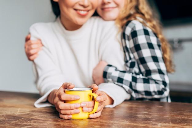 Colheita de mulheres abraçando enquanto está sentado na mesa Foto gratuita