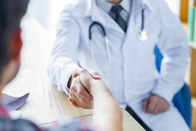 Colheita médico e paciente apertando as mãos no escritório Foto gratuita
