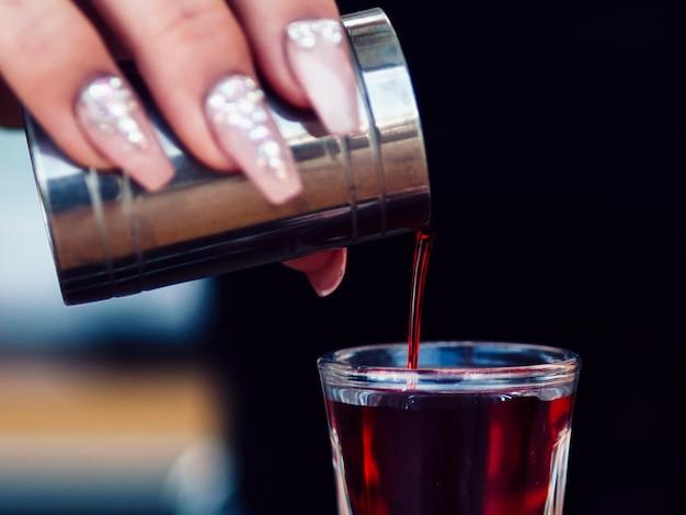 Colheita mulher mão adicionando bebida em tiro Foto gratuita