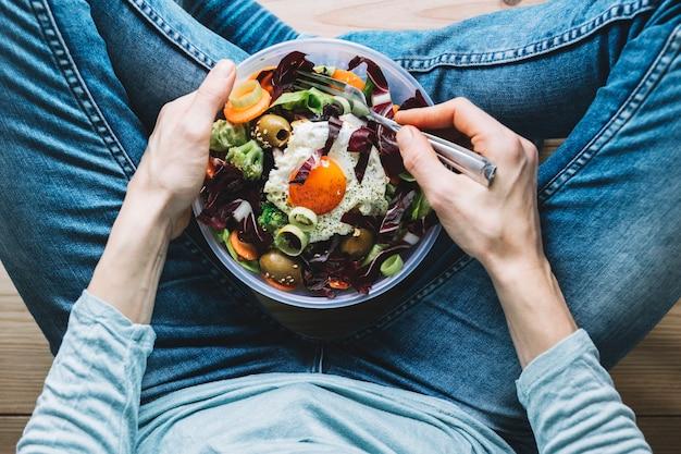 Colheita, pessoa, comer, salada, com, ovo frito Foto gratuita