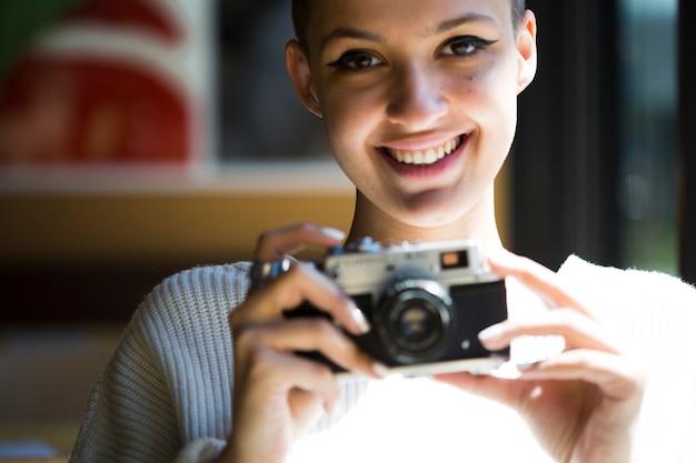Colheita sorridente fotógrafo feminino com câmera vintage Foto gratuita