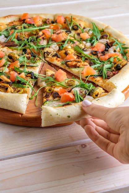 Colhendo à mão uma fatia de pizza com camarão, mexilhão e salmão Foto Premium