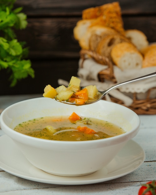 Colher com canja de galinha com legumes e endro Foto gratuita