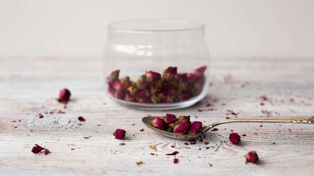 Colher de close-up com mini rosas aromáticas Foto gratuita
