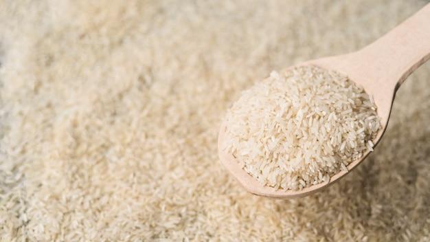 Colher de madeira cheia de arroz cru sobre o cenário de arroz embaçada Foto gratuita