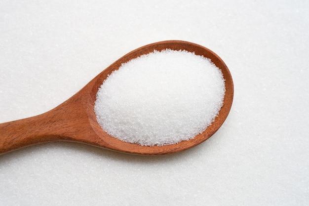 Colher de madeira com açúcar granulado branco. Foto Premium