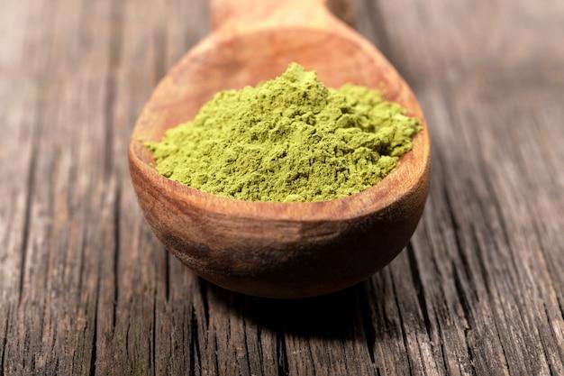 Colher de madeira com pó verde japonês do chá do matcha na placa de madeira resistida dilapidada velha. Foto Premium