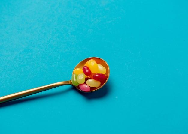 Colher de ouro com doces na parede azul Foto Premium