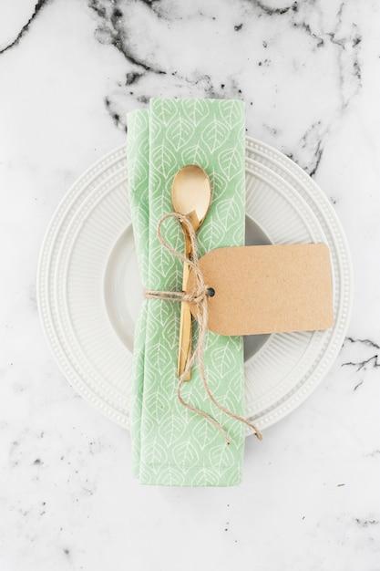 Colher de ouro e guardanapo amarrado com corda na chapa branca contra pano de fundo texturizado Foto gratuita