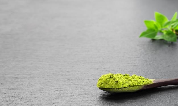 Colher de pau com chá verde matcha em pó Foto Premium