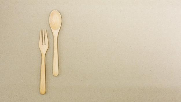 Colher de pau e garfo em papel pardo - fundo Foto Premium